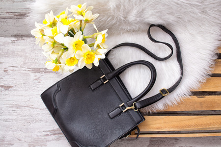 Large black female bag on white fur, daffodils. Fashionable concept, top view