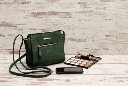 Green ladies handbag, phone, eyeshadow palette and a lipstick on a wooden background. fashion concept