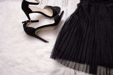 Part of a black pleated skirt and black shoes. Fashion concept. Close-up