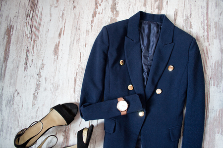 Blue jacket, watch and shoes on a wooden background. Fashion concept