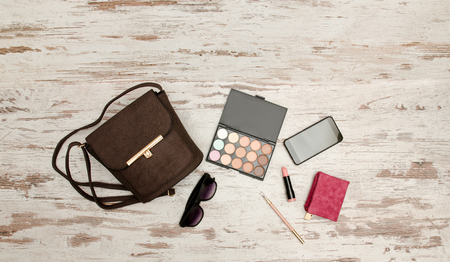closet: Fashionable concept: eyeshadows, handbag, glasses, mobile phone, lipstick, wallet on a wooden background. top view