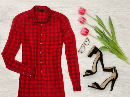 closet: Part of a red checkered blouse, tulips, glasses, lipstick. Fashion concept, close up