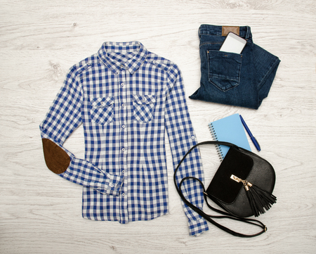 closet: Blue and white plaid shirt, jeans, mobile phone, notebook with pen and black bag. Wooden background. Fashionable concept, top view Stock Photo