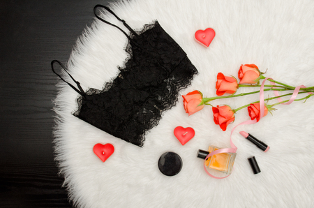 Black lace top, bouquet of orange roses, candles, perfume. Fashionable concept. Top view Stock Photo