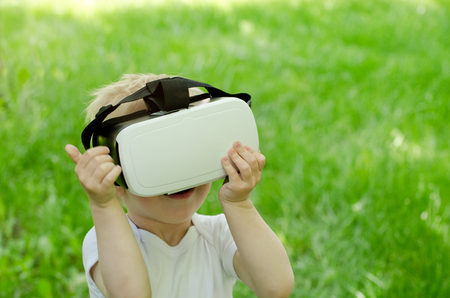 Little boy in a virtual reality helmet on a background of green grass