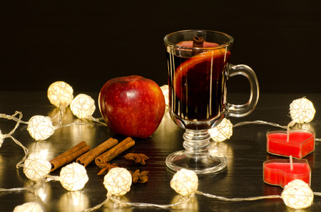 bougie coeur: Mug of mulled wine with spices, candles in the shape of a heart, cinnamon sticks, star anise. Illumination of rattan lanterns on a black wooden table