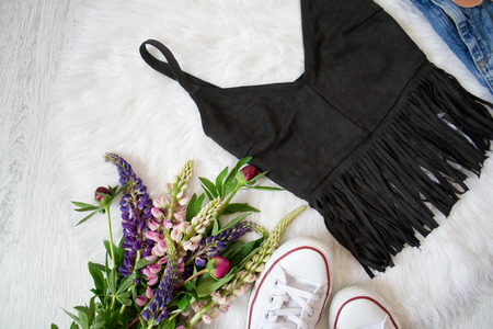 Black suede top with fringe on white fur, a bouquet of flowers, sneakers. Fashionable concept