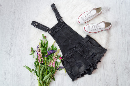 lupines: Gray denim overalls, a bouquet of flowers, sneakers. Fashionable concept Stock Photo