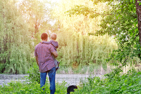 Dad with a small son are standing on the shore of a forest lake, rear view Stock Photo