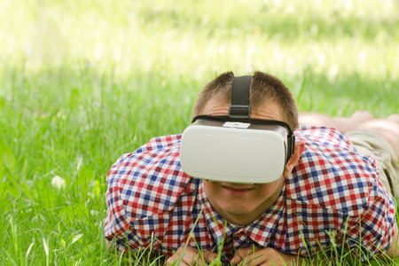 virtual reality simulator: Man in a helmet of virtual reality lies on a green grass