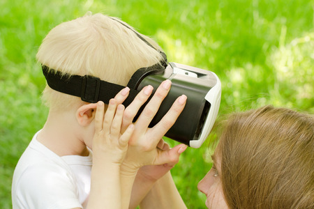 virtual reality simulator: Mom corrects his son glasses of virtual reality against the background of green grass Stock Photo