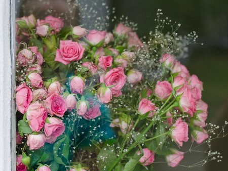 Bouquet of small pink roses behind the glass Stock Photo
