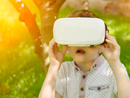 virtual reality simulator: Boy in a virtual reality helmet on a background of green forest. Toning