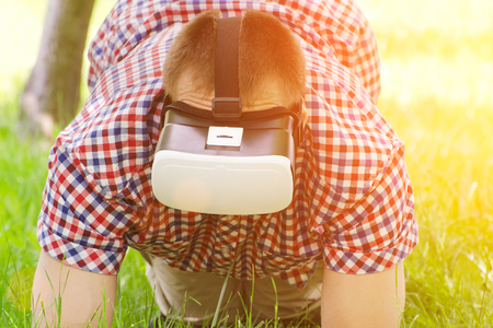 virtual reality simulator: Guy with glasses of virtual reality stands on his knees on the green grass