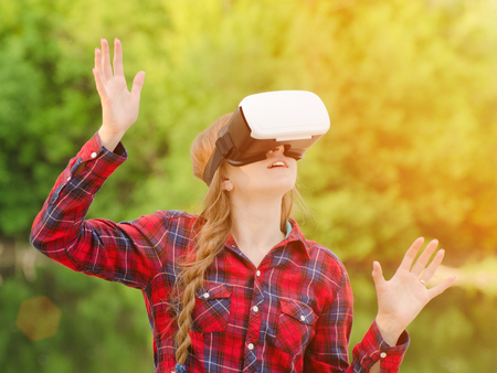 virtual reality simulator: Girl in the helmet of virtual reality against the background of nature. Hands up Stock Photo