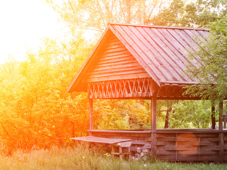 Wooden gazebo in the forest. Summer, sunset
