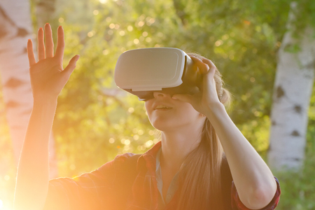 virtual reality simulator: Girl in the helmet of virtual reality against the background of nature Stock Photo