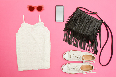 clutch bag: White lace top, black handbag, white sneakers, glasses and phone. Bright pink background. Fashionable concept Stock Photo