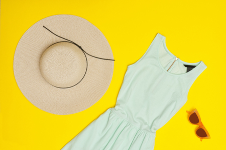Fashionable concept. Female summer wardrobe. Mint dress, hat, glasses. Yellow background, top view