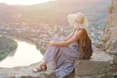 Beautiful girl with backpack and a wide hat sitting and admiring the view of the river, mountains and the city below