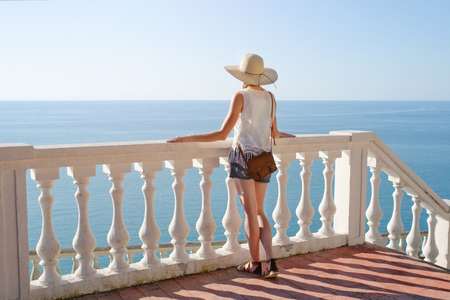 Girl in hat standing on the stairs and looking at the sea. View from the back Stock Photo
