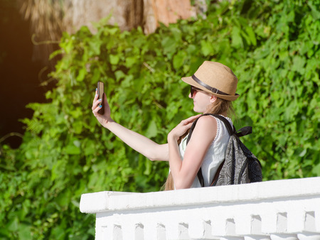Girl in a hat and with a backpack makes selfie in the park Stock Photo