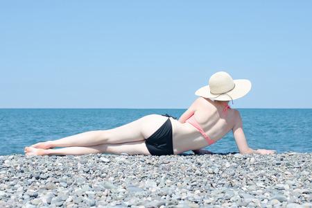 ない日焼け少女は、帽子とビーチに位置し、はだし。背面図 写真素材