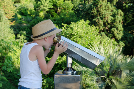 Boy in a hat looking into a large pair of binoculars. Green on the background Stock Photo