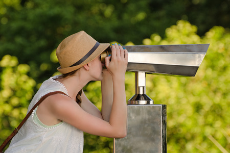 Girl in hat looks into big binoculars. Park in the background