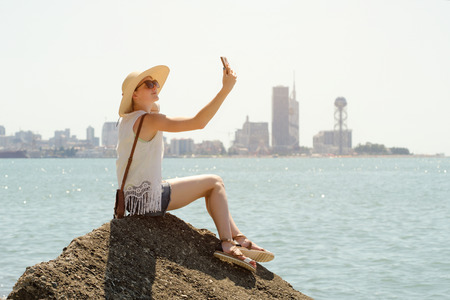 Girl in a hat makes a selfie sitting on a rock by the sea. City in the distance. Sunny day