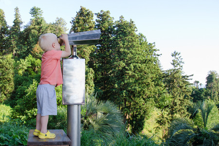 Little blond boy looking in a large pair of binoculars. Park in the background