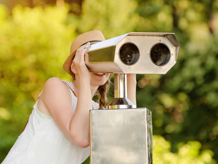 Girl in the hat looks into the big binoculars. Green on the background. Front view Stock Photo