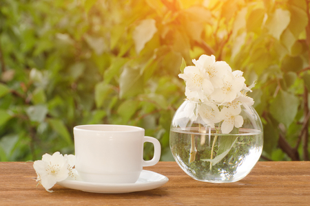 White mug of tea and a vase with jasmine on a wooden table, greens on the background Stock Photo