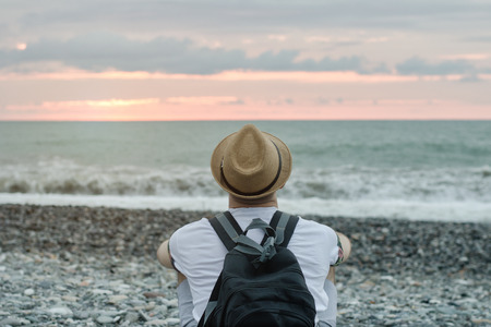 Young man in hat and with backpack sitting on the beach against the backdrop of the sea and sunset sky. Back view