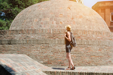 Girl in a hat and with a backpack standing near a brick dome. Sunny day