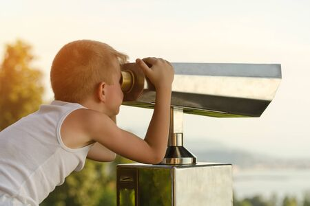Boy looks at the big binoculars. Sky on background