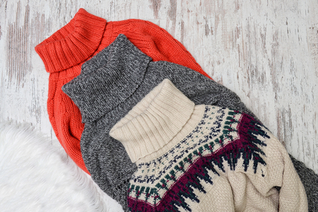winter fashion: Three warm sweaters for neck on a wooden background. Fashion concept.