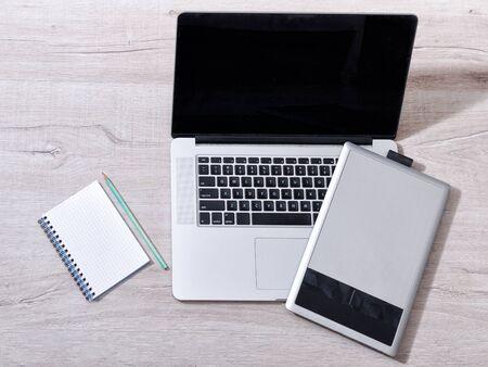 Open de laptop, grafische tablet en notitieblok met pensel op een lichte tafel, bovenaanzicht