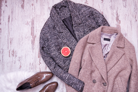 Two woolen coat, brown patent leather shoes on a white fur, half a grapefruit, a wooden background. Fashion concept. top view