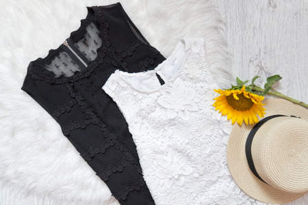 luxurious: Black and white lace dresses, hat and sunflower on white fur. Fashionable concept, top view