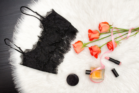 Black lace top on white fur and a bouquet of orange roses and cosmetic. Fashionable concept. Top view