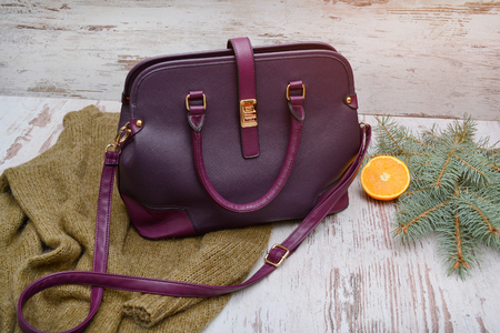 Fashion concept. Purple ladys bag, warm sweater on a wooden background, spruce branch and orange Фото со стока