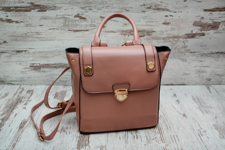 Dark pink bag on a wooden background. Fashionable concept.