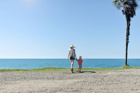 Mom and son stand with their backs against the background of a tall palm tree, sea and blue sky