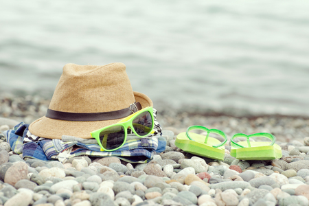 flip flops: Hat, glasses and flip flops on the pebble beach. Sea in the background