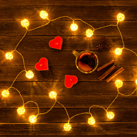 Top view of mulled wine with spices, candles in the shape of a heart, cinnamon sticks, star anise on a wooden table. Garland of lanterns. Stock Photo