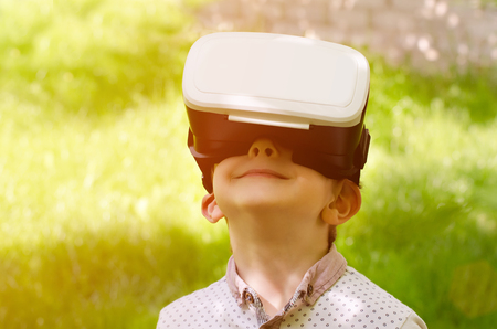 virtual reality simulator: Boy in a virtual reality helmet on a background of green grass