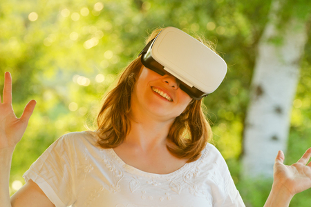 virtual reality simulator: Girl in the helmet of virtual reality against the background of nature. Toning