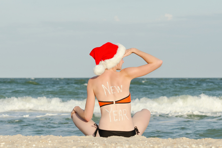 Girl in Santa hat with the inscription New Year on the back is sitting on the beach and looks into the distance Stock Photo