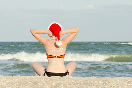Girl in a santa hat with an inscription New Year on her back sitting on the seashore Stock Photo